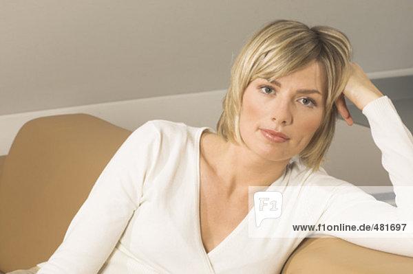 Portrait selbstsicher junge Frau sitzt auf couch