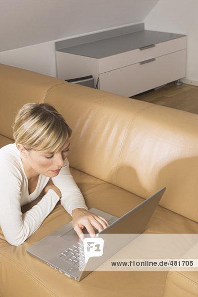 erhöhte Ansicht blonde Frau arbeiten mit Notebook-Computer im Wohnzimmer