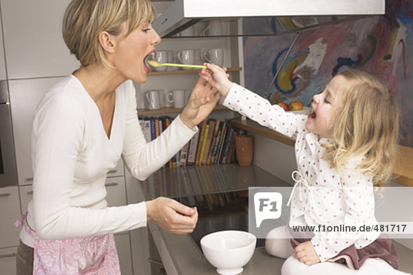 kleines Mädchen Fütterung ihrer Mutter in Küche
