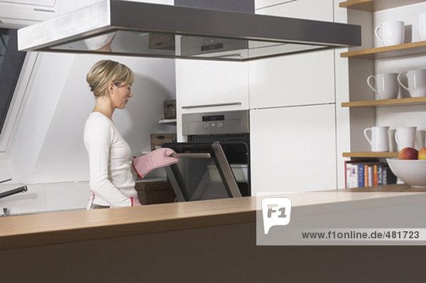 zeigen Sie in Küche mit Hausfrau öffnen Ofentür an