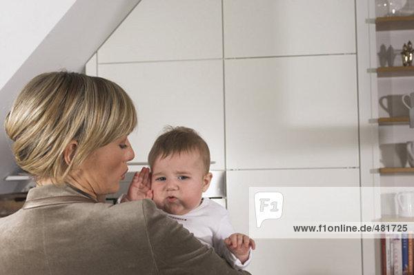 Heckansicht gestresster junge geschäftsfrau hält baby