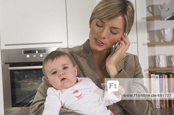 Porträt der jungen geschäftsfrau in Küche hält Baby und sprechen auf Handy