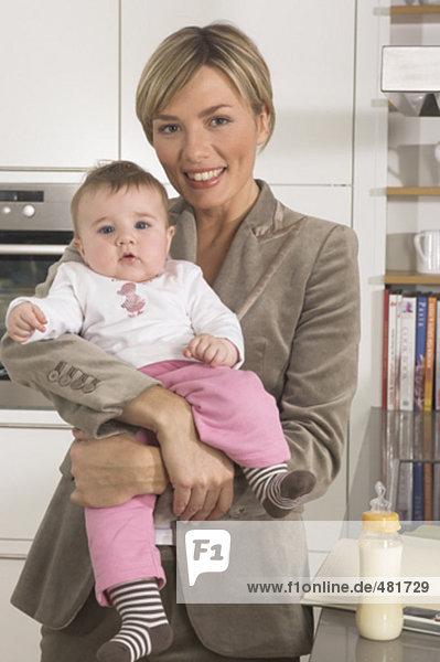 Porträt von stolz young Geschäftsfrau with Baby in Küche