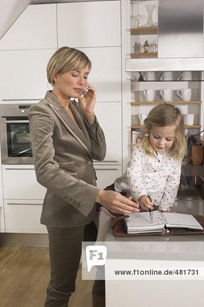 junge geschäftsfrau stehen in Küche und sprechen auf Handy während Tochter mit ihrem Tagebuch spielt