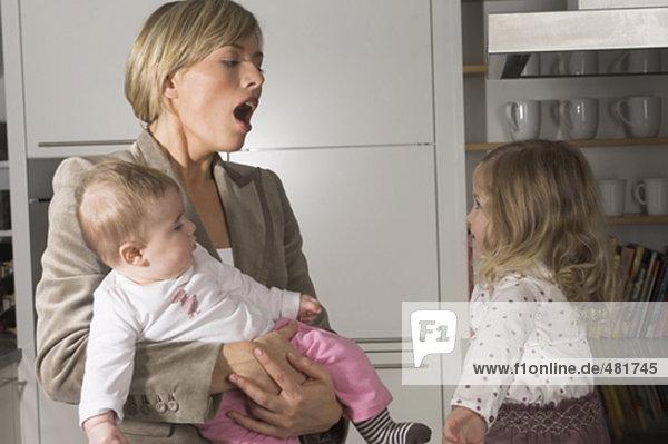 gähnen junge geschäftsfrau betrachten ihrer kleinen Tochter