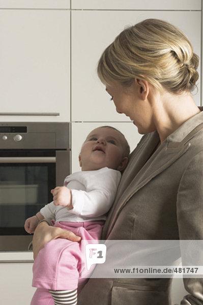 Porträt der jungen geschäftsfrau lächelnd auf ihrer kleinen Tochter baby