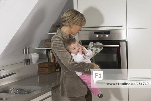 junge geschäftsfrau mit ihrem Baby stehen auf der Backofen