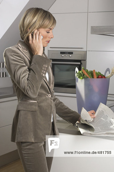 Porträt der jungen geschäftsfrau in Küche stehen  sprechen auf Handy und lesen Zeitung