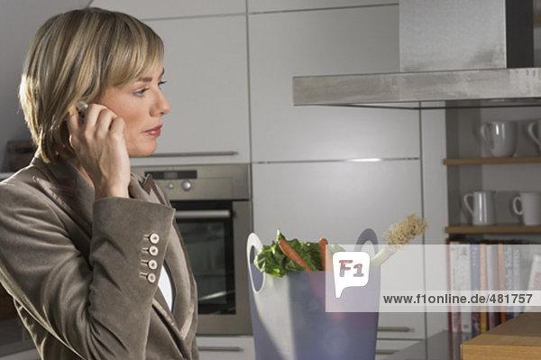 Porträt der jungen geschäftsfrau stehen in Küche und sprechen auf Handy