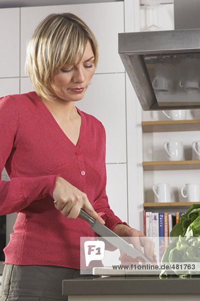 portrait of young woman preparing meal in kitchen  cutting red pepper
