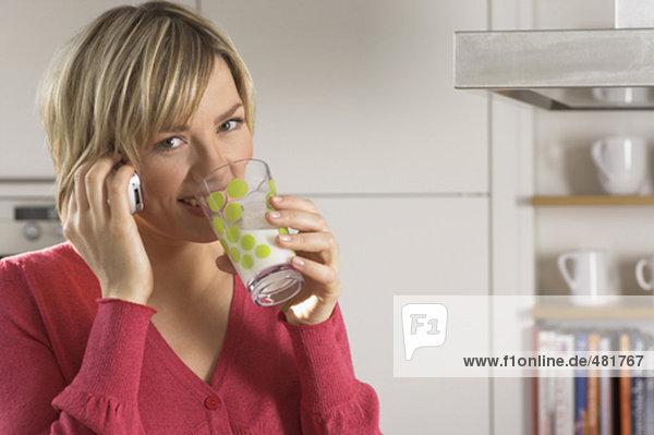 Portrait einer jungen Frau mit Handy  trinken Glas Milch in Küche