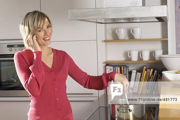 Portrait einer jungen Frau Kochen und sprechen auf Handy