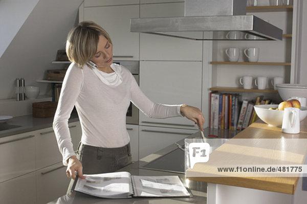 Portrait einer jungen Frau in Küche sprechen auf Handy  Kochen und lesen Magazin