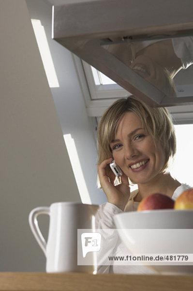 Portrait einer jungen Frau mit Handy in Küche lächelnd
