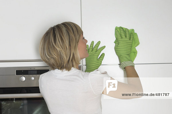 Rückansicht des jungen Frau reinigen Schrank