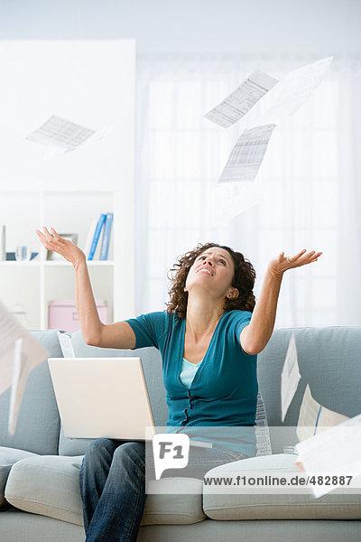 Frau umgeben von Rechnungen