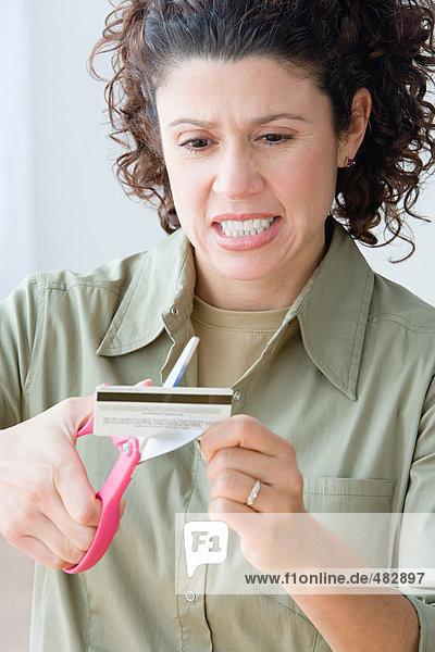 Frau  die eine Kreditkarte zerschneidet.