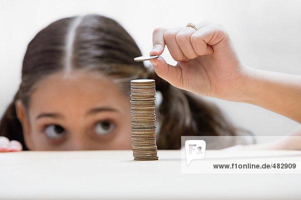 Mädchen legt eine Münze auf den Stapel