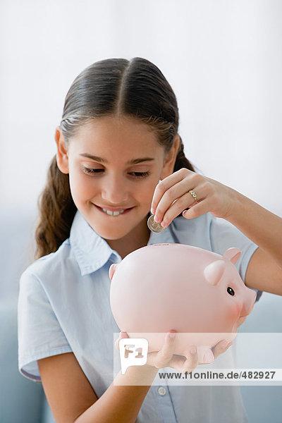 Mädchen rettet eine Münze im Sparschwein