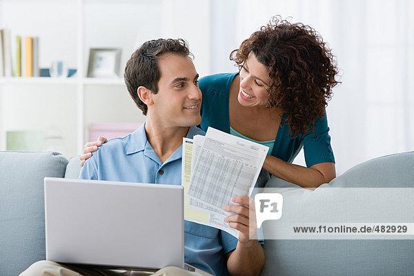Paar  das sich die Finanzen zu Hause am Computer anschaut