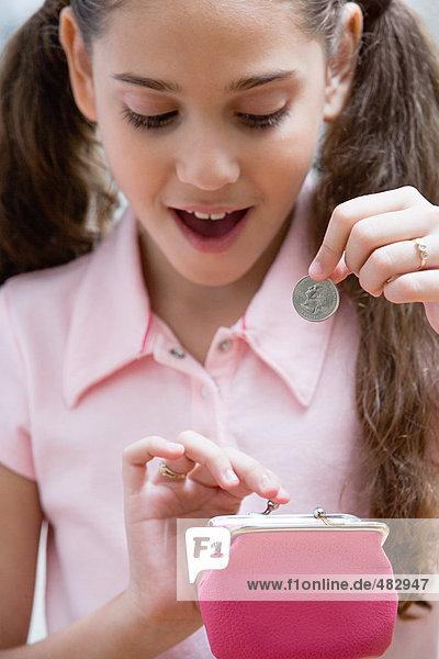 Mädchen mit Münze und Geldbörse