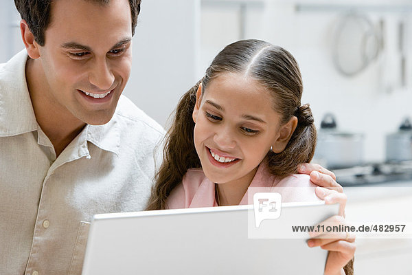 Father and daughter using a laptop computer