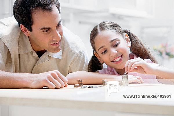 Vater und Tochter mit Münzen