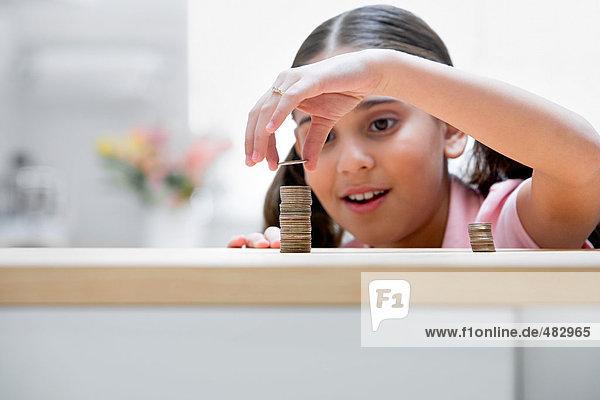 Mädchen legt Münze auf den Stapel