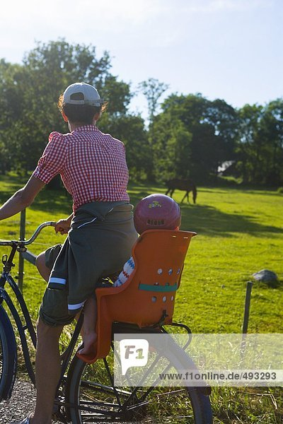 Mutter und Kind auf einem Fahrrad.