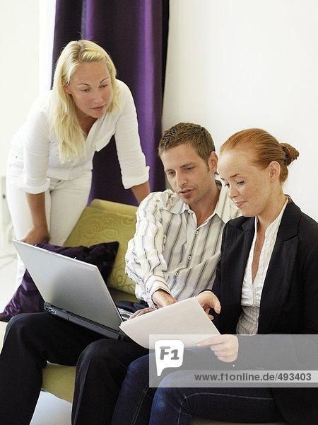 Zwei Frauen und ein Mann in einem Büro.
