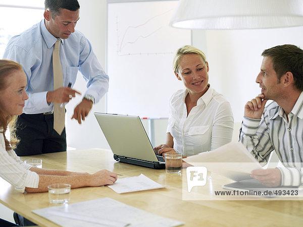 Zwei Frauen und zwei Männer in einem Büro mit einem Treffen.