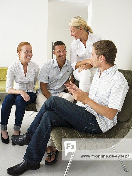 Vier Personen in einem Büro zu sprechen.