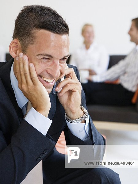 A happy businessman talking in a cellphone.