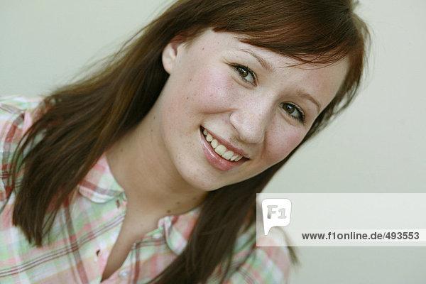 Portrait einer jungen Frau lächelnd.