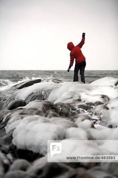 Eine Frau auf Felsen mit Eis bedeckt.