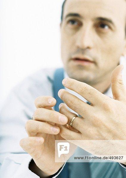 Mann spielt mit Ehering