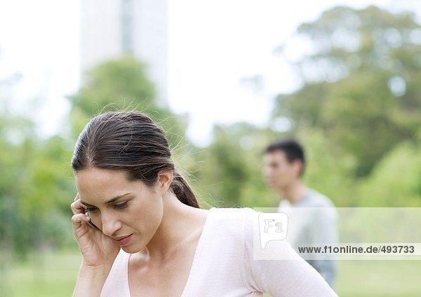 Junge Frau mit Handy im Stadtpark