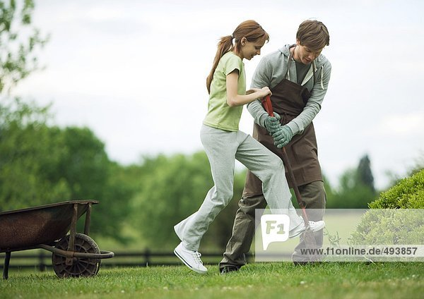 Mann hilft Mädchen graben im Hof