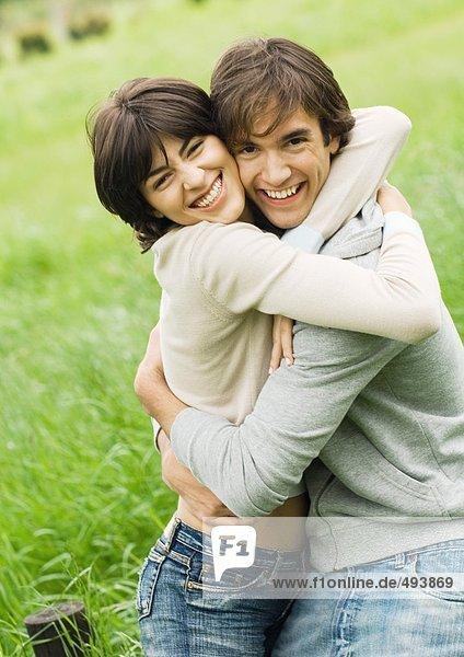 Junges Paar umarmend und lächelnd
