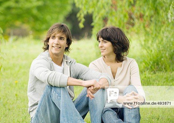 Junges Paar auf Gras sitzend