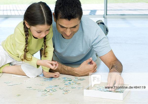 Vater und Tochter beim Zusammenstellen des Rätsels