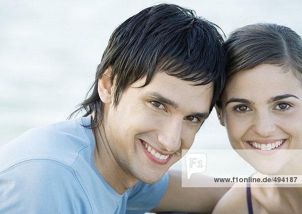 Junges Paar  Kopf an Kopf  lächelnd  Portrait