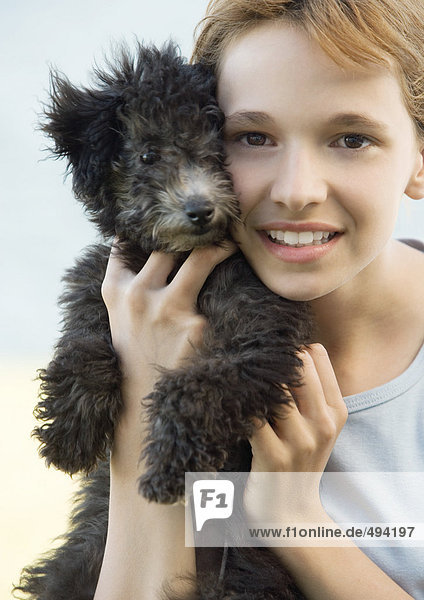 Girl holding puppy up next to face  portrait