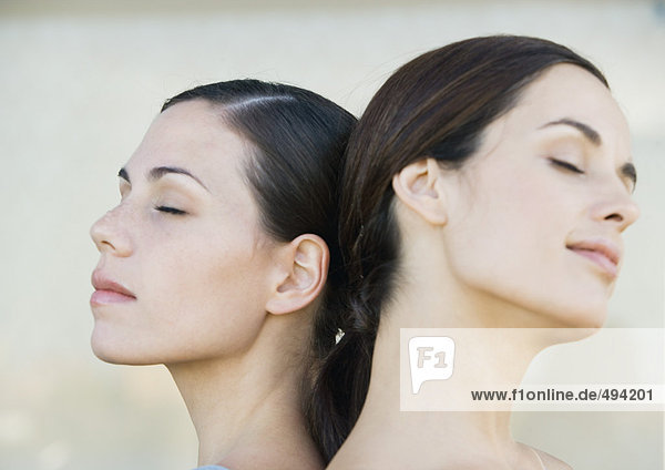 Two young women back to back with eyes closed  side view