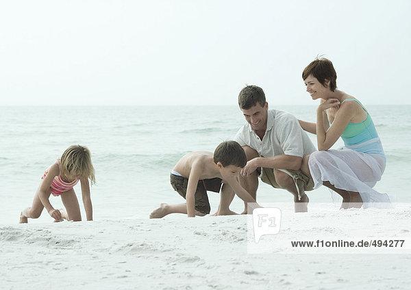Familie am Strand  Kinder spielen auf Sand  während die Eltern zuschauen.