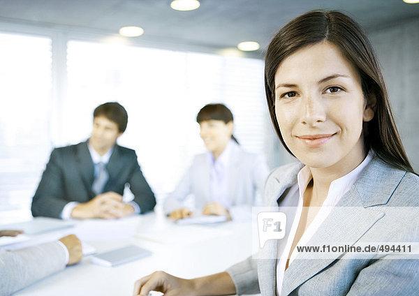 Geschäftsfrau lächelt vor der Kamera  Treffen im Hintergrund