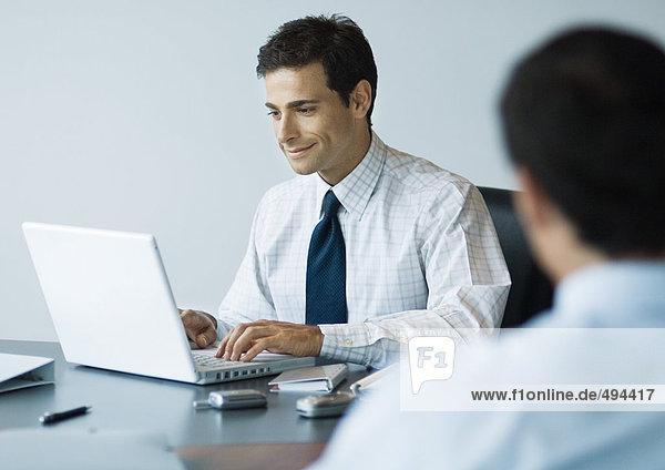 Geschäftsmann am Schreibtisch sitzend mit Laptop