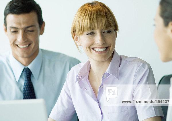 Geschäftskollegen lächeln sich an