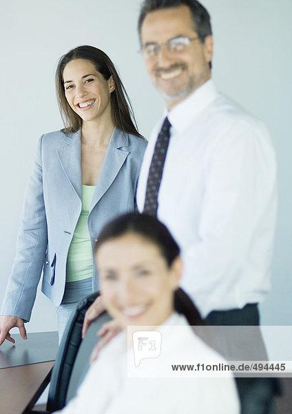 Drei Geschäftskollegen lächeln vor der Kamera  Fokus auf den Hintergrund