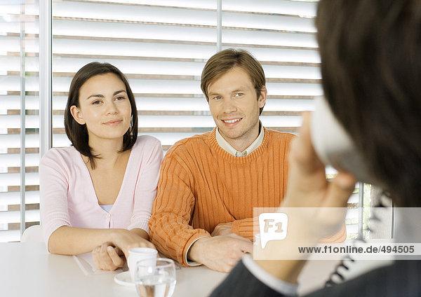 Junges Paar sitzt dem Verkäufer gegenüber